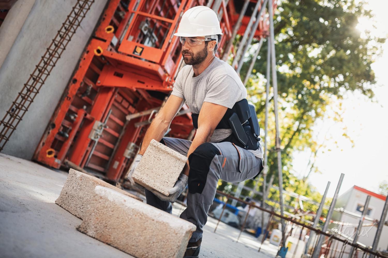ouvrier qui porte une charge lourde avec exosquelette